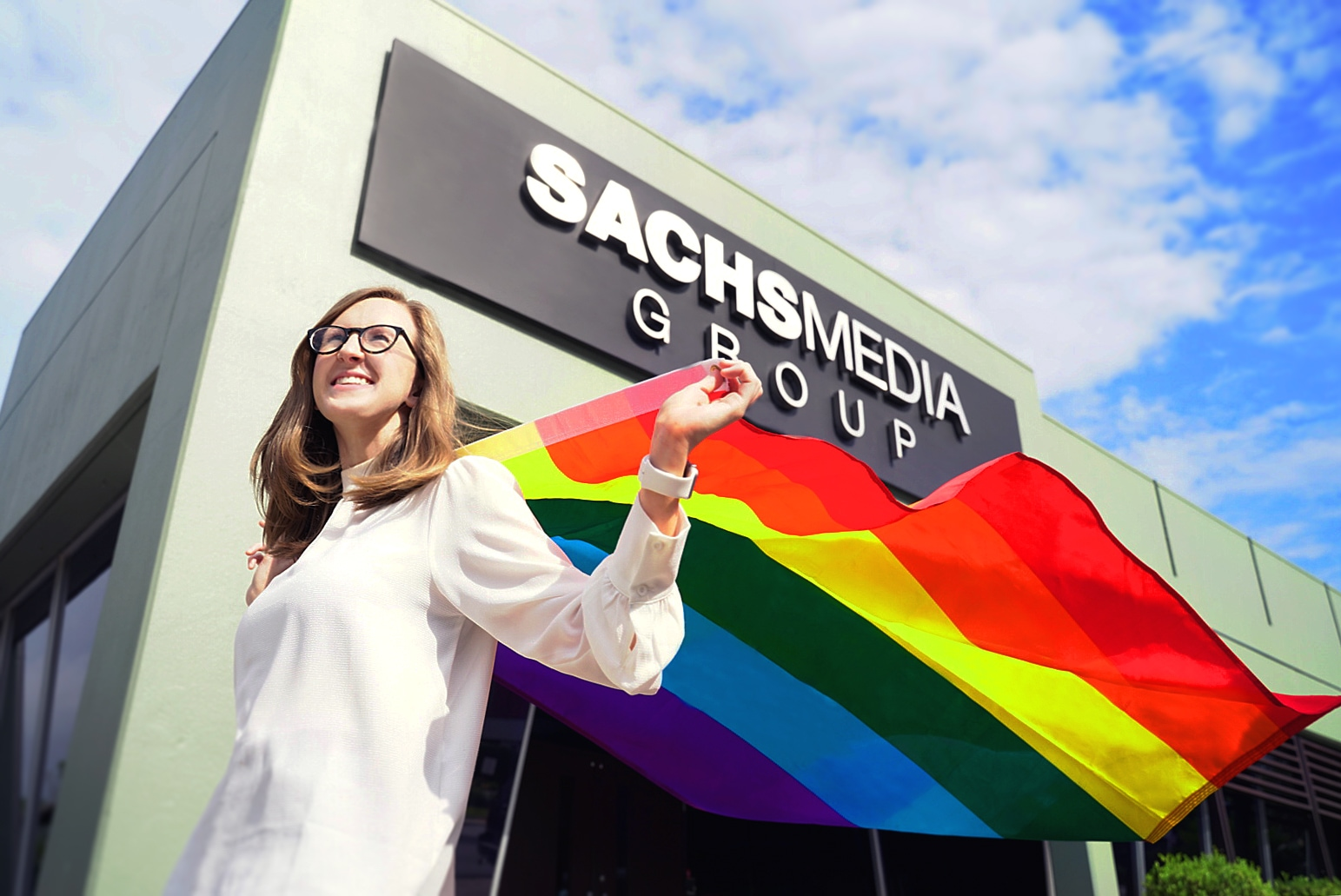 Allison P. Couch, author and Sachs Media Group employee celebrates Pride Month with LGBTQ pride flag