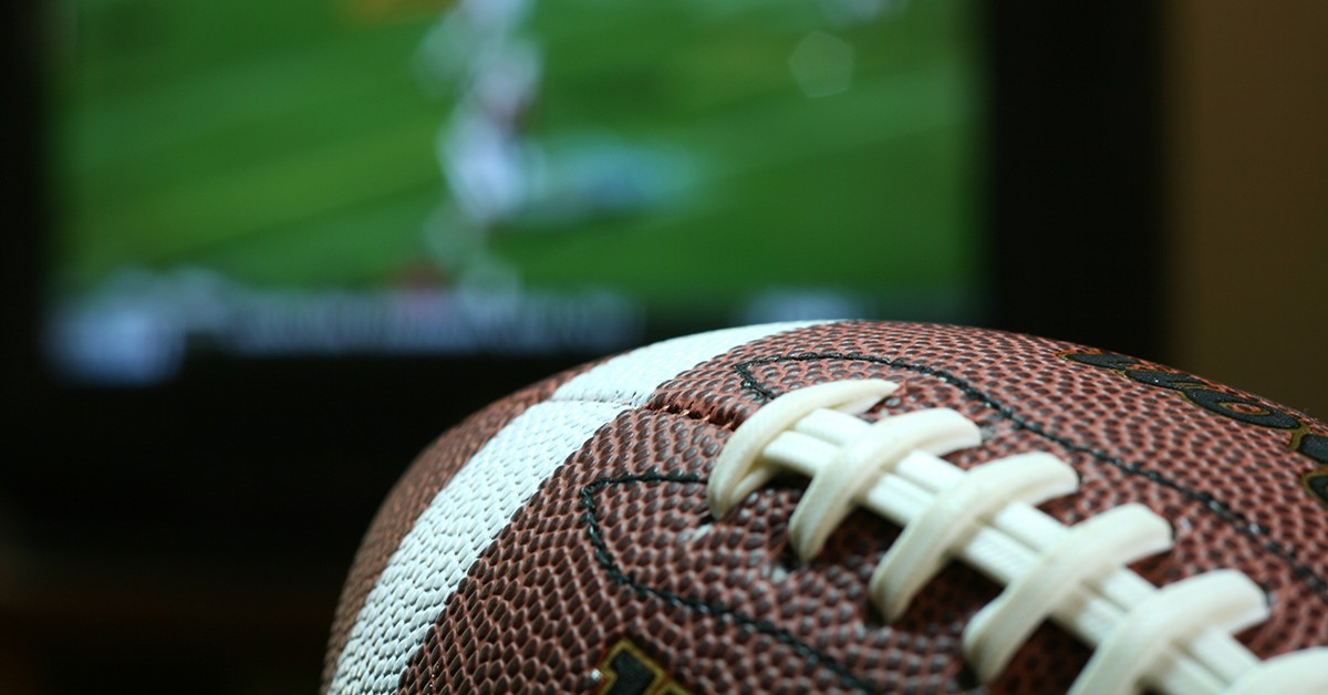 close-up of a football with TV screen in the background